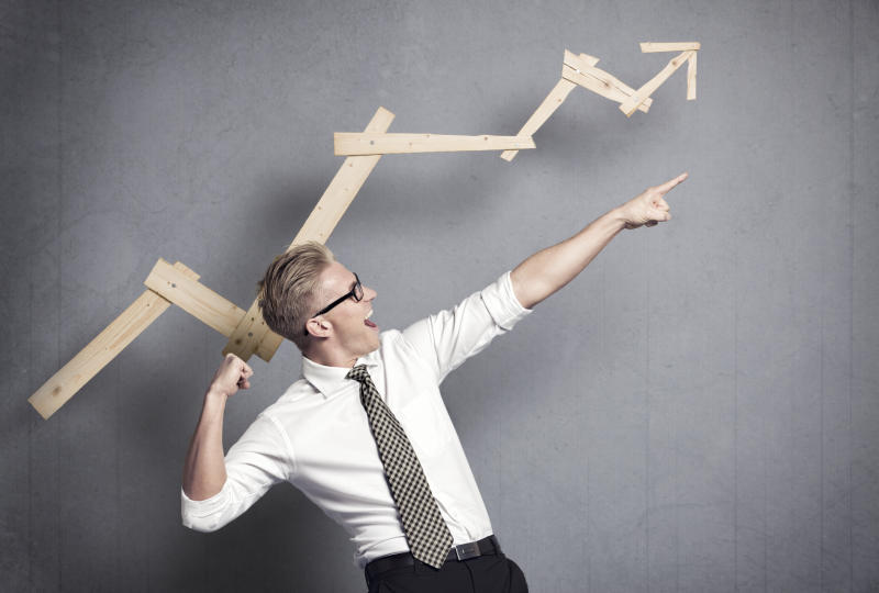 Man in white shirt and tie celebrating in front of wooden arrow chart indicating gains.