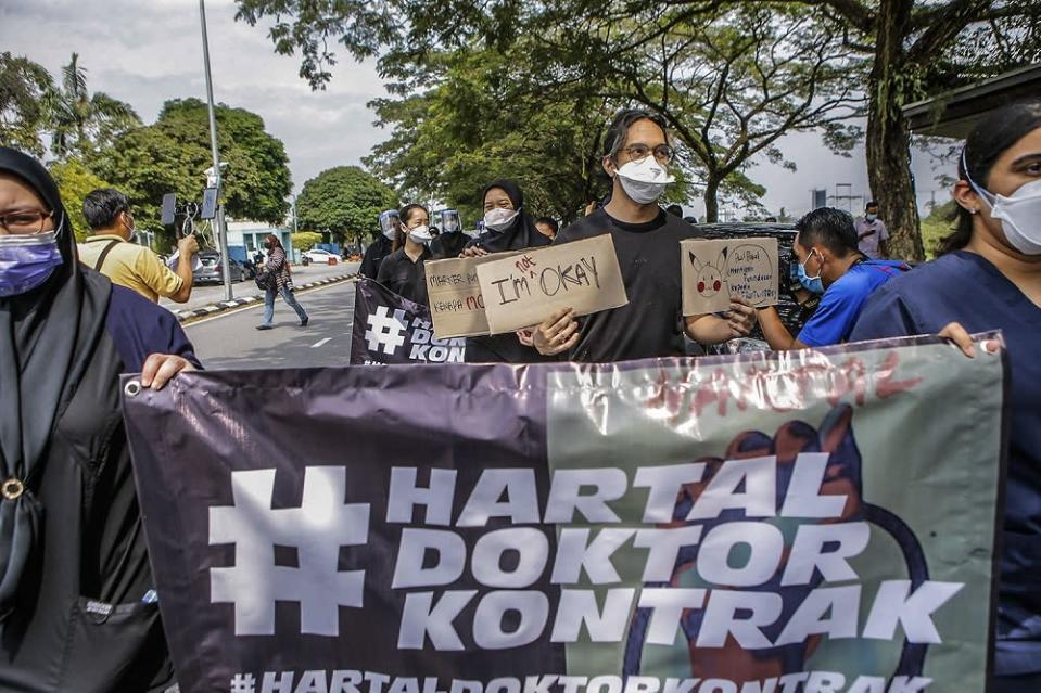 Contract doctors hold aloft placards demanding equal treatment as they go on strike at the Sungai Buloh Hospital July 26, 2021. — Picture by Hari Anggara