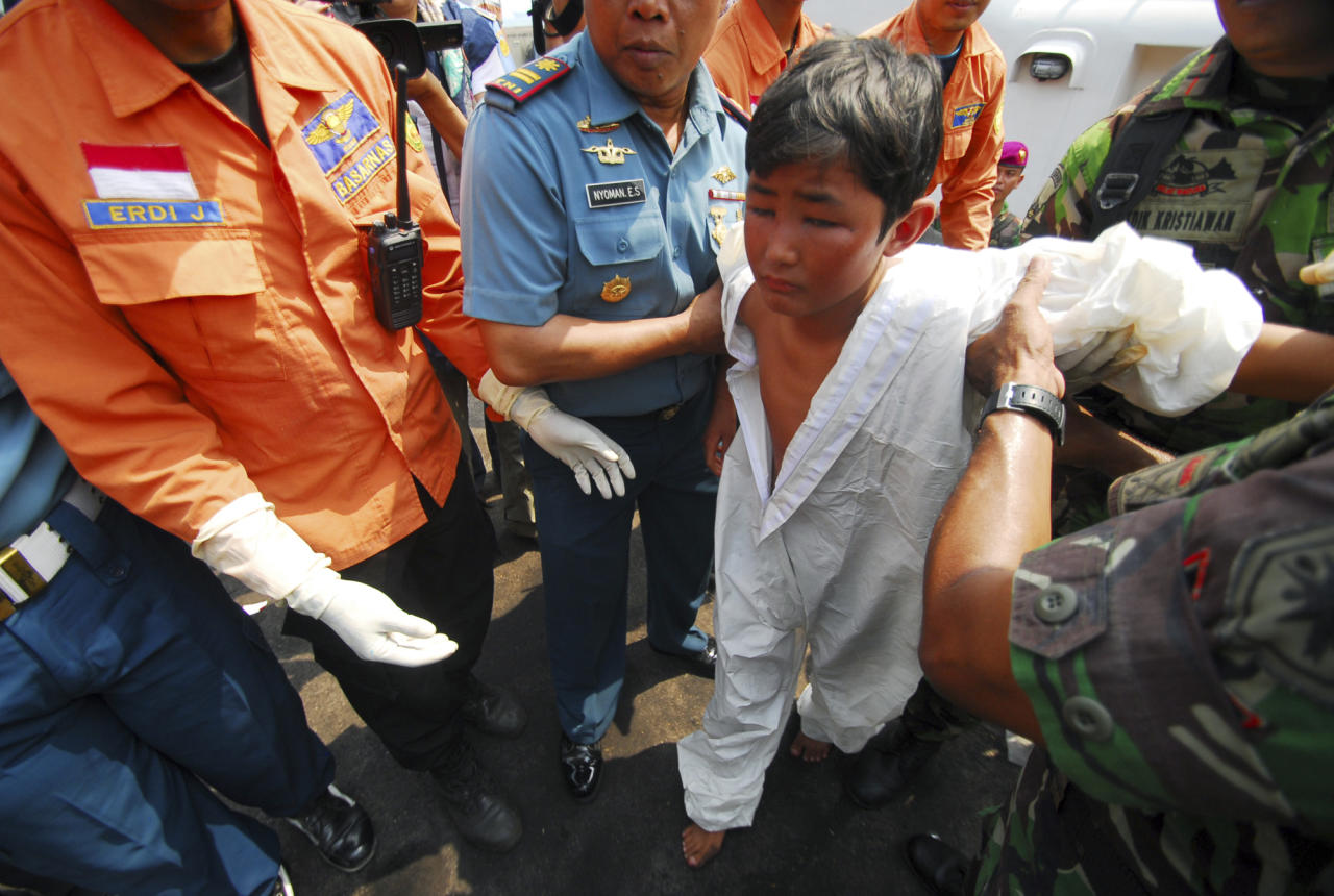 A survivor from a boat reportedly carrying about 150 asylum seekers that sank off Java island, is helped by Indonesian navy officers upon arrival at a port in Merak, Banten province, Indonesia, Friday, Aug. 31, 2012. The wooden fishing boat sank as it headed for a remote Australian island. More than 50 people had been rescued by Friday morning, and one body had been recovered, Australian and Indonesian officials said. (AP Photo)
