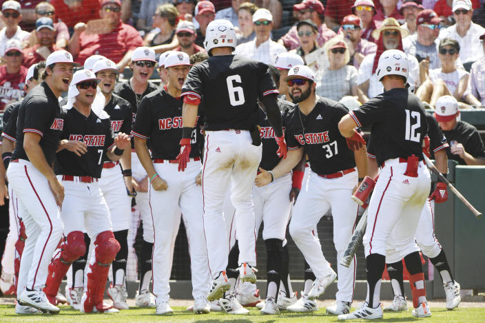 North Carolina State batter Vojtech Mensik (6) is greeted by teammates after hitting a home run against Arkansas in the fourth inning of an NCAA college baseball super regional game Saturday, June 12, 2021, in Fayetteville, Ark. (AP Photo/Michael Woods)