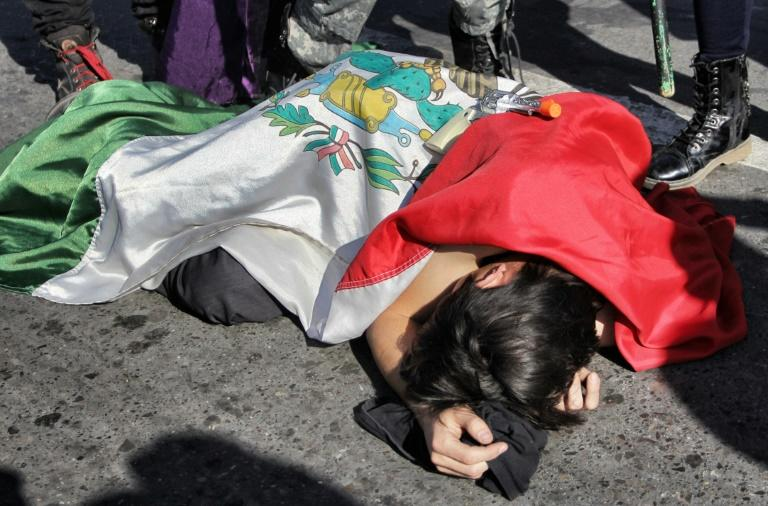 An activist posing as a victim of homicide lies on the ground covered with a Mexican flag during a demonstration against the approval of an Internal Security Law that would grant surveillance powers to the army, at the Paso del Norte International Bridge that links Mexico with the United States in Ciudad Juarez, Chihuahua state, Mexico (AFP Photo/HERIKA MARTINEZ)