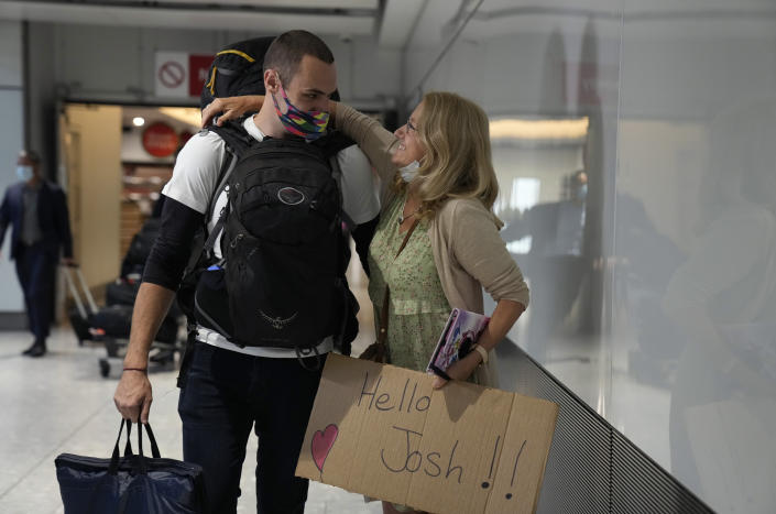 Debbie Greaves embraces her son Josh, who she's not seen for nine month as he arrives on a flight from Sweden, at Terminal 5 of Heathrow Airport in London, Monday, Aug. 2, 2021. Travelers fully vaccinated against coronavirus from the United States and much of Europe were able to enter Britain without quarantining starting today, a move welcomed by Britain's ailing travel industry. (AP Photo/Matt Dunham)