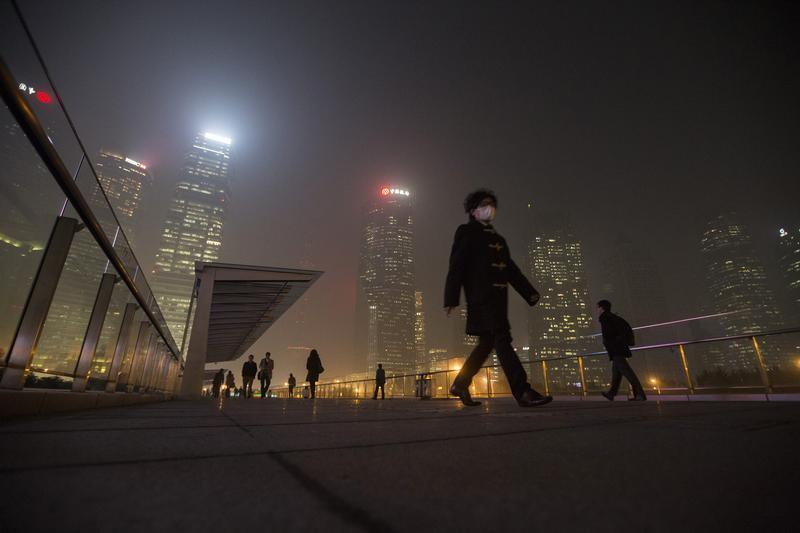 A man wears a mask while walking on a bridge during a hazy night in Shanghai's financial district of Pudong