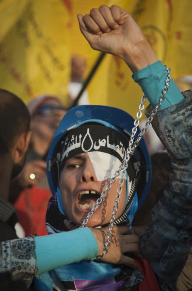 """An Egyptian protester wearing a headband with Arabic writing that reads, """"revenge for the martyrs,"""" chants anti-government slogans during a rally in Tahrir Square in Cairo, Egypt, Friday, Oct. 19, 2012. Several thousand Egyptian protesters are rallying in Cairo to demand the president and his Muslim Brotherhood supporters ensure the country's constitution represents all factions of society. (AP Photo/Khalil Hamra)"""