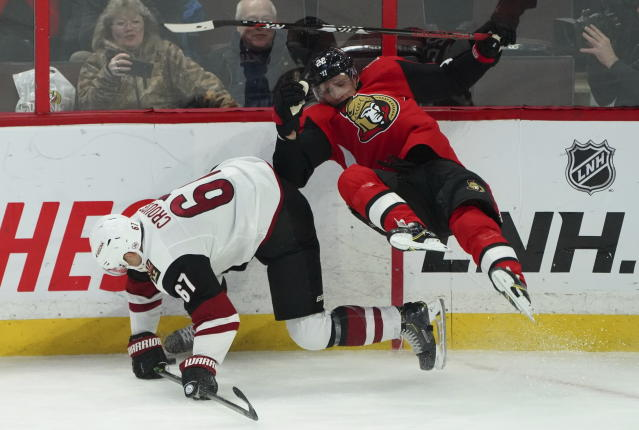 Ottawa Senators defenseman Nikita Zaitsev (22) crashes to the ice while fighting for the puck with Arizona Coyotes left wing Lawson Crouse (67) during third-period NHL hockey game action in Ottawa, Ontario, Thursday, Feb. 13, 2020. (Chris Wattie/The Canadian Press via AP)