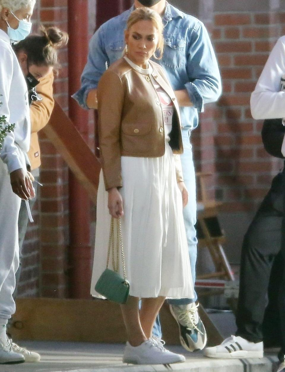 <p>Jennifer Lopez is seen in a leather jacket, a white dress and matching sneakers on the set of a photo shoot in L.A. on Wednesday.</p>