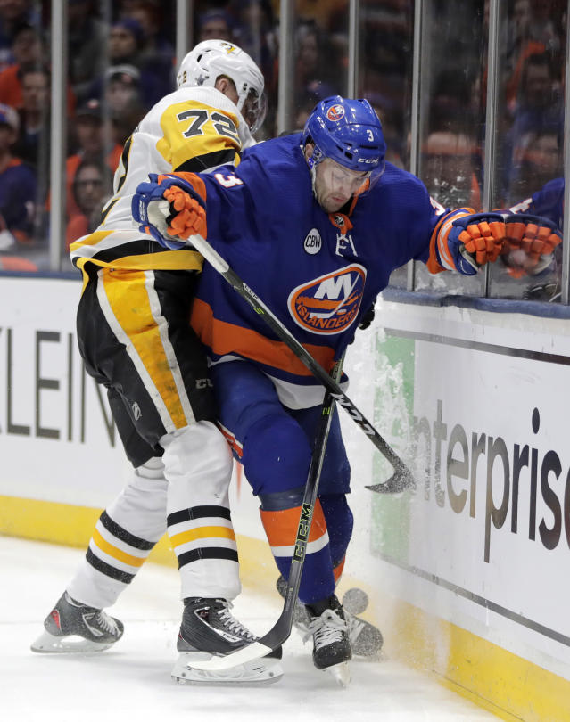 Pittsburgh Penguins right wing Patric Hornqvist (72), of Sweden, and New York Islanders defenseman Adam Pelech (3) compete for possession during the first period of Game 2 of an NHL hockey first-round playoff series Friday, April 12, 2019, in Uniondale, N.Y. (AP Photo/Julio Cortez)