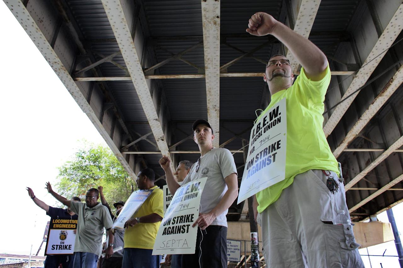 Members of the Brotherhood of Locomotive Engineers and Trainmen (BLET) union and members of the International Brotherhood of Electrical Workers (IBEW) wave to motorist while walking a picket line outside the Roberts Avenue rail yard in Philadelphia on Saturday, June 14, 2014, after the two unions went on strike at midnight Friday. Pennsylvania Gov. Tom Corbett asked President Barack Obama on Saturday to intervene the dispute between the Southeast Pennsylvania Transportation Authority and its engineers and electricians unions. (AP Photo/ Joseph Kaczmarek)