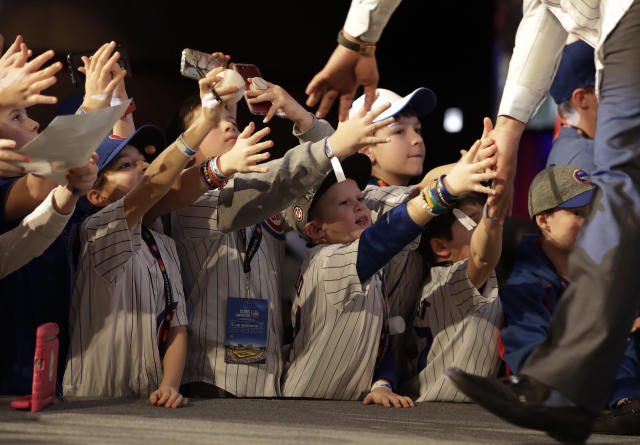 Chicago Cubs fans reach for the hands of Anthony Rizzo at the baseball team's annual convention Friday, Jan. 12, 2018, in Chicago. (AP Photo/Charles Rex Arbogast)