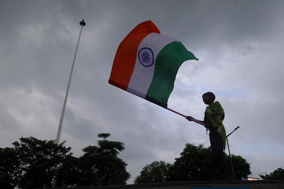 A boy sells Tricolour flags on the eve of Independence Day at Connaught Place. (Photo by Naveen Sharma/SOPA Images/LightRocket via Getty Images)
