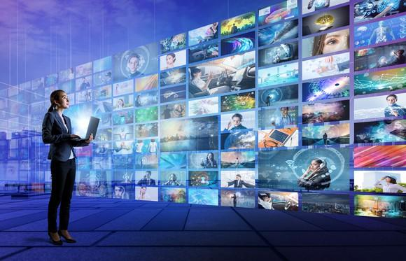Woman holding a PC looks at a wall of TV screens.