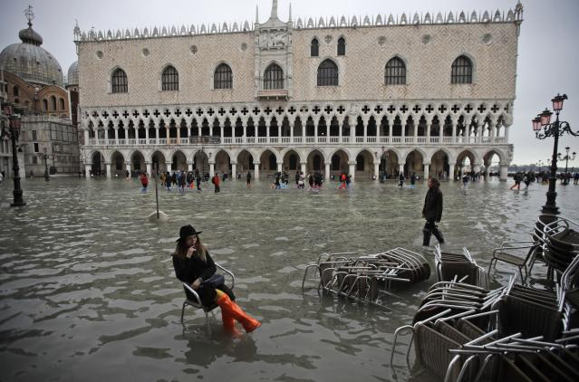 A woman sits in a chair in a flooded St. Mark's Square, in Venice, Wednesday, Nov. 13, 2019. The high-water mark hit 187 centimeters (74 inches) late Tuesday, Nov. 12, 2019, meaning more than 85% of the city was flooded. The highest level ever recorded was 194 centimeters (76 inches) during infamous flooding in 1966. (AP Photo/Luca Bruno)