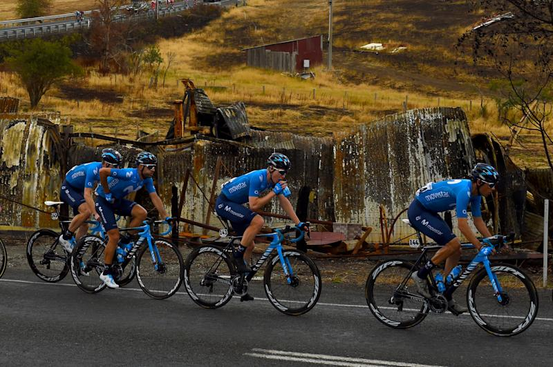 The Movistar team races past a burned-out outbuilding during stage 3 of the 2020 Tour Down Under