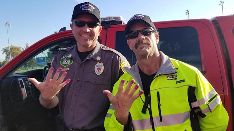 North Davis Fire District firefighters Allen Hadley and Kevin Lloyd show off their purple manicures given to them by a nervous young girl in Utah.