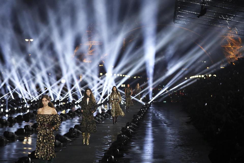 FILE - In this Sept.24, 2019 file photos, models wear creations as part of the Saint Laurent Ready To Wear Spring-Summer 2020 collection, unveiled during the fashion week, in Paris. Gucci and St. Laurent are two of the highest profile fashion houses to announce they will leave the fashion calendar behind, with its relentless four-times a year rhythm, shuttling cadres of fashionistas to global capitals where they squeeze shoulder-to-shoulder around runways for 15 breathless minutes. The coronavirus lockdown -- which has hit luxury fashion houses on their bottom lines -- has also given pause to rethink the pace of fashion. (Photo by Vianney Le Caer/Invision/AP, File)