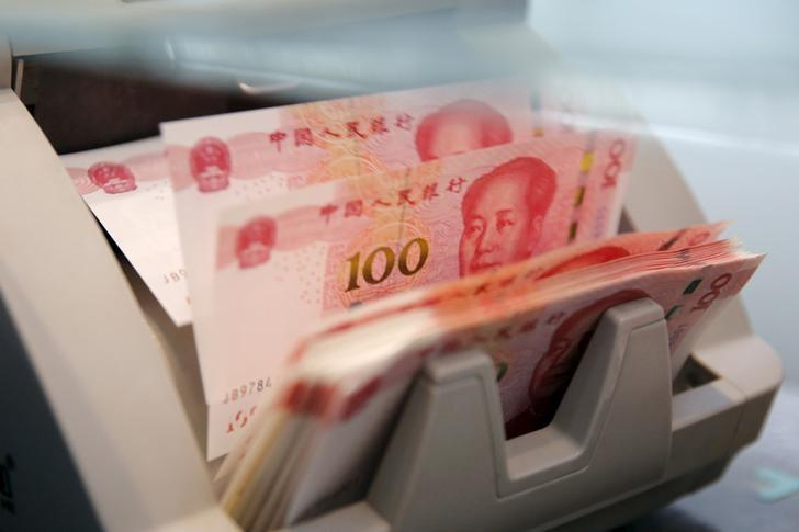 File picture of Chinese 100 yuan banknotes in a counting machine while a clerk counts them at a branch of a commercial bank in Beijing