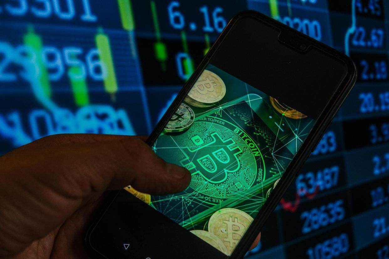 POLAND - 2021/05/18: In this photo illustration a Bitcoin logo seen displayed on a smartphone with stock market percentages in the background. (Photo Illustration by Omar Marques/SOPA Images/LightRocket via Getty Images)