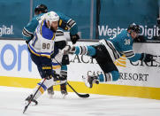 San Jose Sharks defenseman Mario Ferraro (38) is checked into the boards by St. Louis Blues center Ryan O'Reilly (90) during the second period of an NHL hockey game in San Jose, Calif., Saturday, Feb, 27, 2021. (AP Photo/Tony Avelar)
