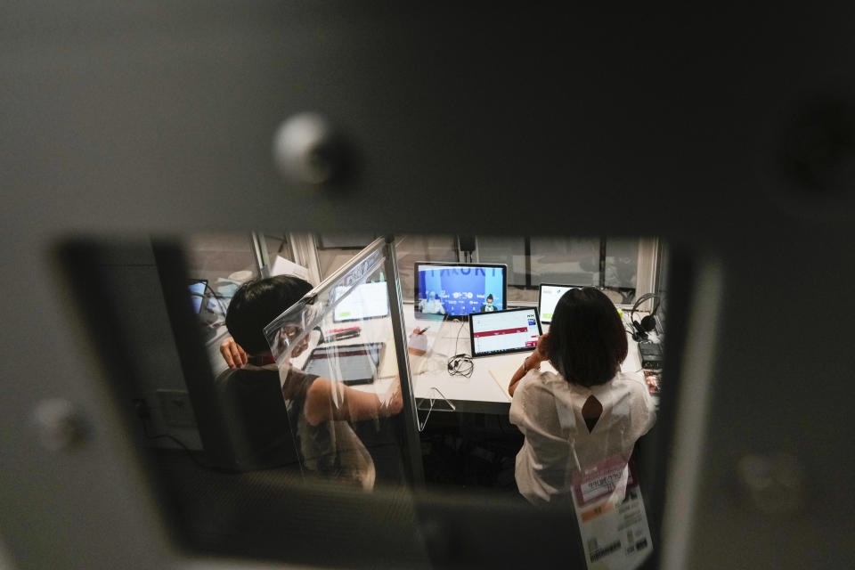 Interpreters work at the main press center during the 2020 Summer Olympics, Friday, July 30, 2021, in Tokyo, Japan. Unlike previous Olympics, all the interpretation is being done remotely with most interpreters working in booths at the main center. About two dozens interpreters aren't even in the country, chiming in from the Americas or Europe to handle late night events in Japan. (AP Photo/Luca Bruno)
