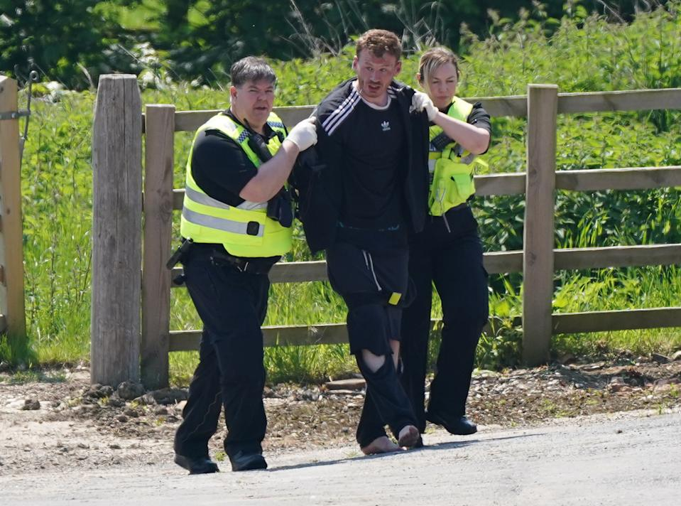 A man is detained at Hallington House Farm, on the outskirts of Louth, Lincolnshire, by officers hunting for Daniel Boulton, who is sought in connection with the deaths of a 26-year-old woman and her nine-year-old son on Monday. Picture date: Tuesday June 1, 2021.