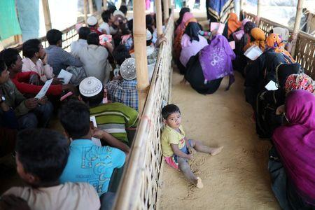A Rohingya child sits on the floor while his mother waits in a queue to collect aid supplies in Kutupalong refugee camp in Cox's Bazar