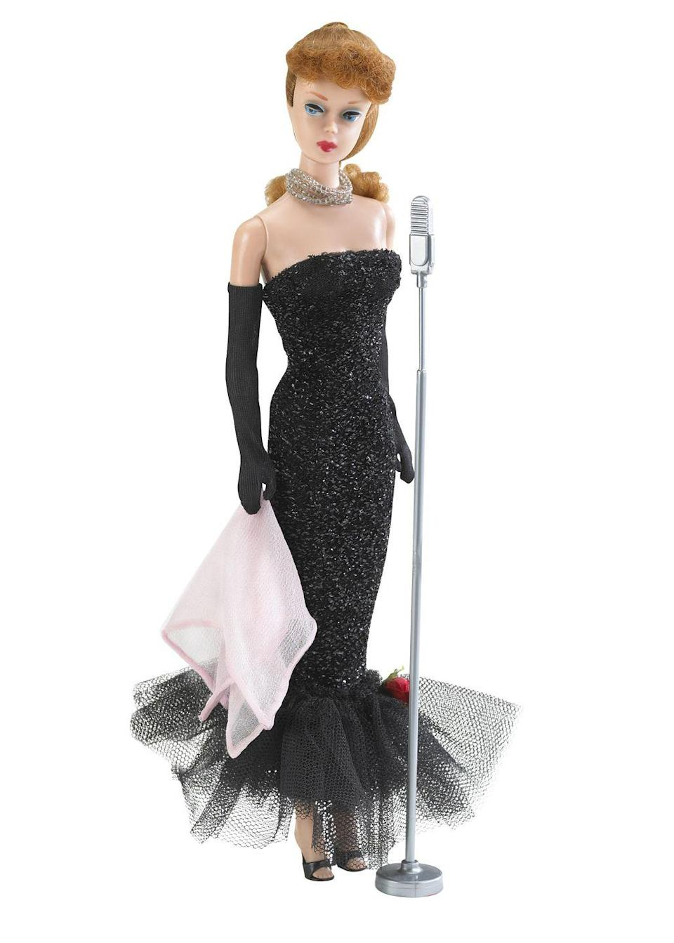 "<p>With her strapless black dress and long gloves, Barbie Solo In The Spotlight becomes one of the more glamorous dolls ever. </p><p><a href=""http://www.goodhousekeeping.com/life/g2530/barbie-dolls-history-facts/"" rel=""nofollow noopener"" target=""_blank"" data-ylk=""slk:18 things you didn't know about Barbie »"" class=""link rapid-noclick-resp""><em>18 things you didn't know about Barbie »</em></a></p>"