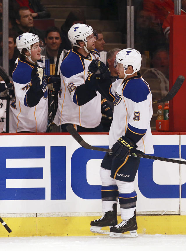 St Louis Blues' Jaden Schwartz, right, celebrates with teammates T.J. Oschie, left, and David Backes after scoring a first period goal against the Chicago Blackhawks in an NHL hockey game in Chicago on Sunday, April 6, 2014. (AP Photo/Charles Cherney)
