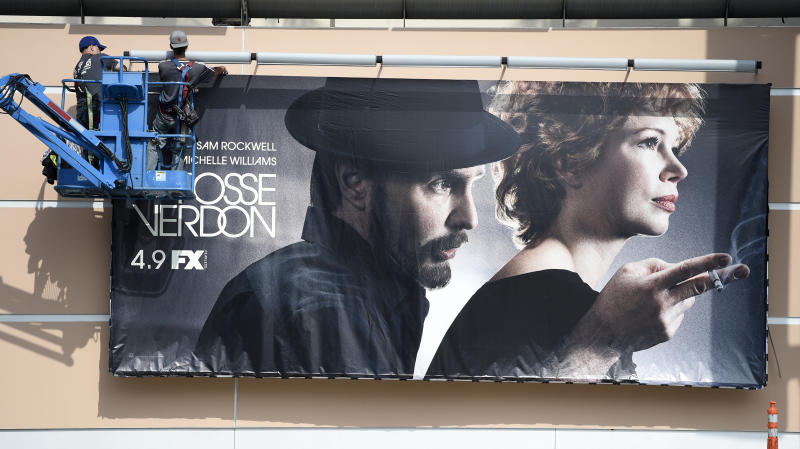 "Workers put up a poster for the upcoming FX limited series ""Fosse/Verdon"" near the entrance to Fox Studios, Tuesday, March 19, 2019, in Los Angeles. Disney's $71.3 billion acquisition of Fox's entertainment assets is set to close around 12 a.m. EDT on Wednesday.(AP Photo/Chris Pizzello)"