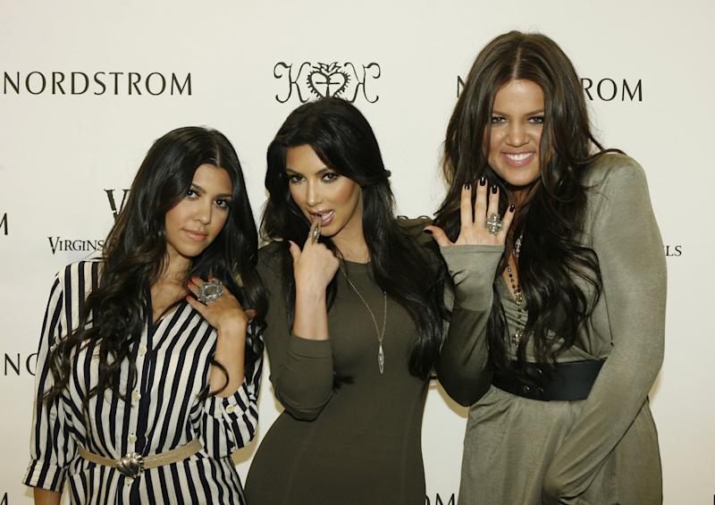 Kourtney posing with Kim and Khloe at a Nordstrom event