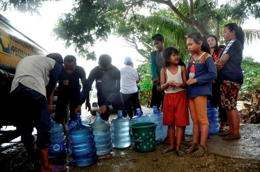 People wait to get fresh water from a truck in their flood affected village in Bekasi, West Java