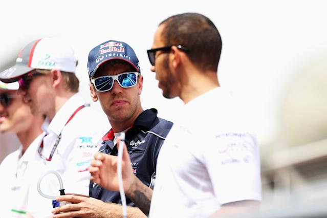 SAKHIR, BAHRAIN - APRIL 21: Sebastian Vettel (C) of Germany and Infiniti Red Bull Racing talks with Lewis Hamilton (R) of Great Britain and Mercedes GP while attending the drivers parade before the Bahrain Formula One Grand Prix at the Bahrain International Circuit on April 21, 2013 in Sakhir, Bahrain. (Photo by Mark Thompson/Getty Images)