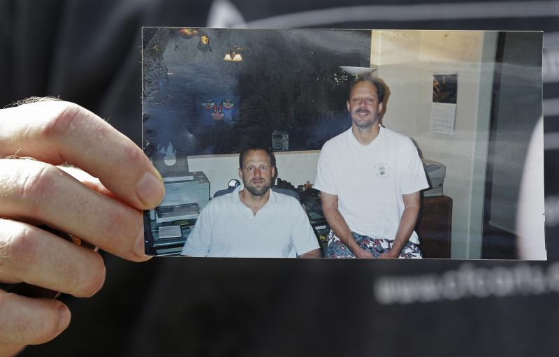 This Oct. 2, 2017 file photo, shows Eric Paddock holding a photo of himself, at left, and his brother, Stephen Paddock, at right, outside his home in Orlando, Florida. He's among recent mass shooters who've legally obtained and owned weapons because of limited weapons laws, lapses in the background check process or law enforcement's failure to heed warnings of concerning behavior. (AP Photo/John Raoux, File)