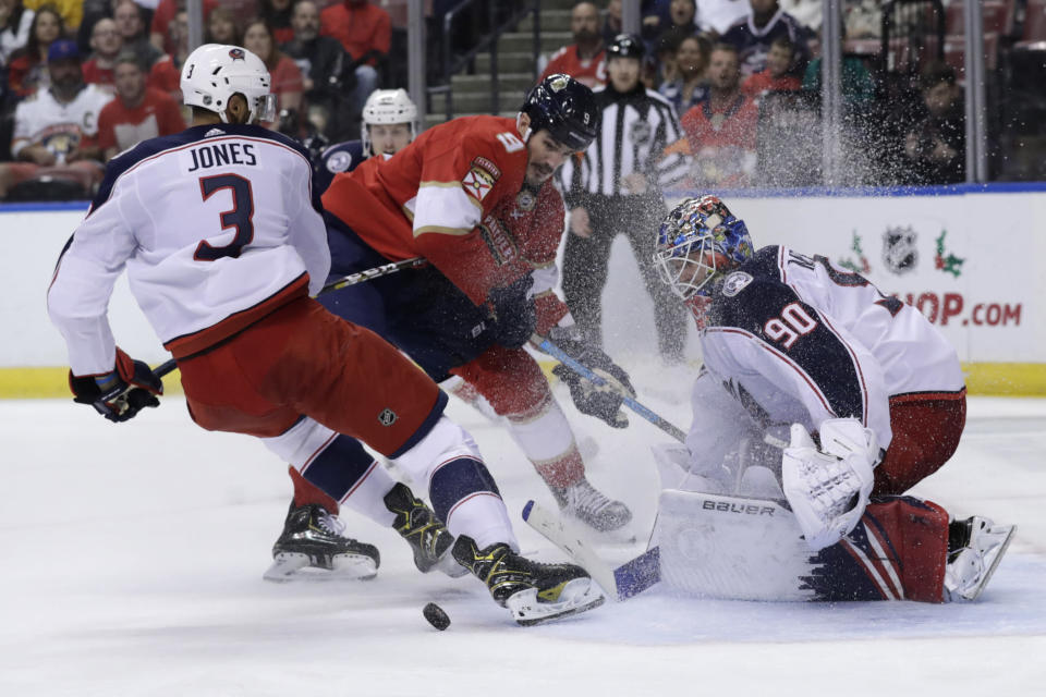 Columbus Blue Jackets goaltender Elvis Merzlikins (90) defends the goal as Blue Jackets defenseman Seth Jones (3) and Florida Panthers center Brian Boyle (9) fight for the puck during the second period of an NHL hockey game, Saturday, Dec. 7, 2019, in Sunrise, Fla. (AP Photo/Lynne Sladky)