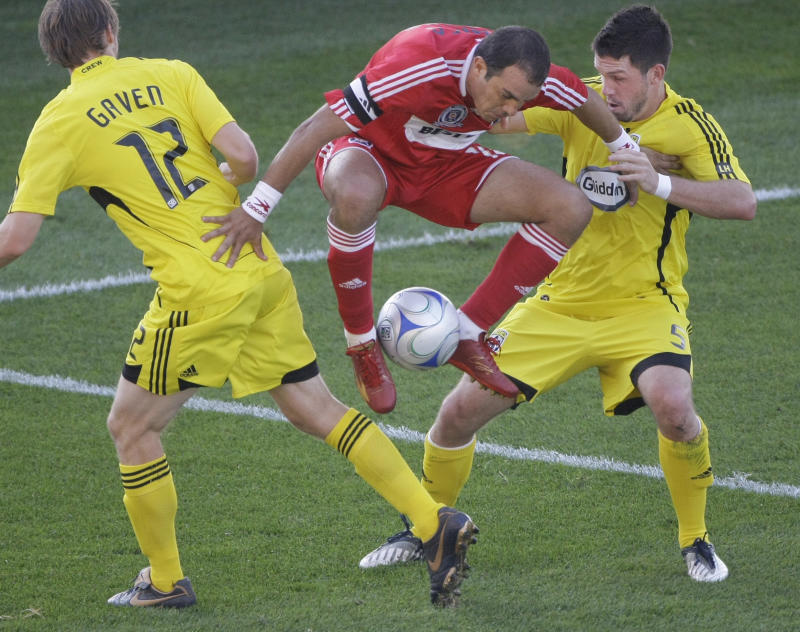 Chicago Fire's Cuauhtemoc Blanco, center, carries the ball over the legs of Columbus Crew's Eddie Gavin, left, and Danny O' Rourke, right, with both feet during the first half of an MLS match in Bridgeview, Ill., Sunday, Oct. 12, 2008. (AP Photo/Charles Rex Arbogast)