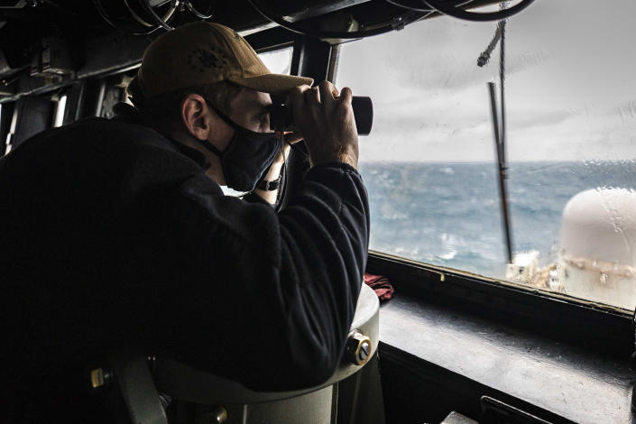 In this Dec. 30, 2020, file photo provided by U.S. Navy, Ensign Grayson Sigler, from Corpus Christi, TX., scans the horizon while standing watch in the pilot house as guided-missile destroyer USS John S. McCain conducts routine underway operations in support of stability and security for a free and open Indo-Pacific, at the Taiwan Strait. As China flexes its muscle in the Taiwan Strait and the Asia-Pacific region, Taiwan has become a regional flashpoint, as Japan, the United States and other democracies develop closer ties with the self-ruled island that Beijing regards as a renegade territory to be united by force if necessary. (Mass Communication Specialist 2nd Class Markus Castaneda/U.S. Navy via AP, File)