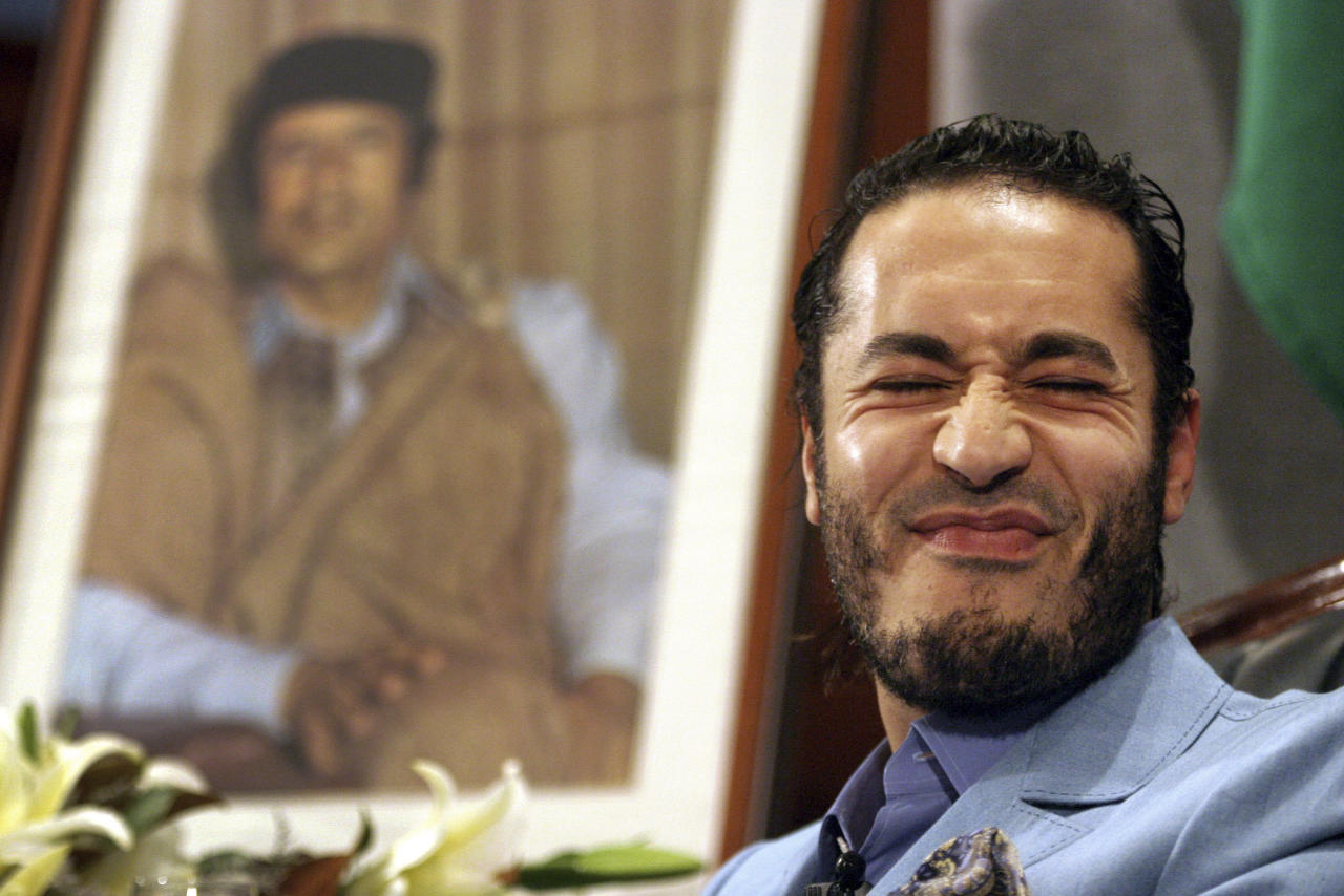 """FILE -- In this file photo of Monday, Feb. 7, 2005 Al-Saadi Gadhafi, the son of Libyan leader Moammar Gadhafi, reacts in front of the leader's portrait during a press conference in Sydney, Australia. The spokesman for Niger's government announced Sunday Sept, 11, 2011 that Libyan leader Moammar Gadhafi's son Al-Saadi has entered the country via the northern desert separating the landlocked African nation from Libya. Amadou Morou, who is also the minister of justice, told reporters at a news conference Sunday: """"I wish to announce to you that one of Gadhafi's sons _ Al-Saadi Gadhafi _ was intercepted in the north of Niger.""""(AP Photo/Dan Peled, file)"""