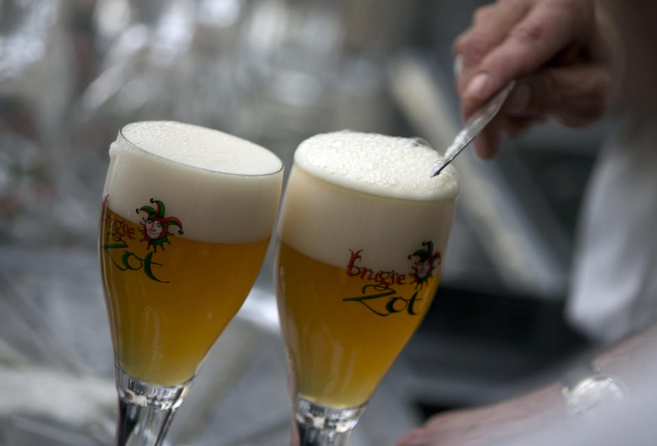 FILE - In this file photo dated Thursday, May 26, 2016, a workers scrapes the foam off of a glass of beer before serving, in Bruges, Belgium. Bars and restaurants in Belgium will be allowed to reopen starting Monday June 8, 2020, under strict coronavirus conditions, with tables spaced at least 1.5 meters apart, with patrons being asked to support their locals. (AP Photo/Virginia Mayo, FILE)