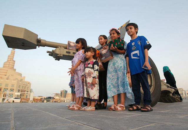 <p>Children pose for a picture beside a traditional Ramadan cannon in Doha, Qatar, June 6, 2017. (Photo: Naseem Zeitoon/Reuters) </p>