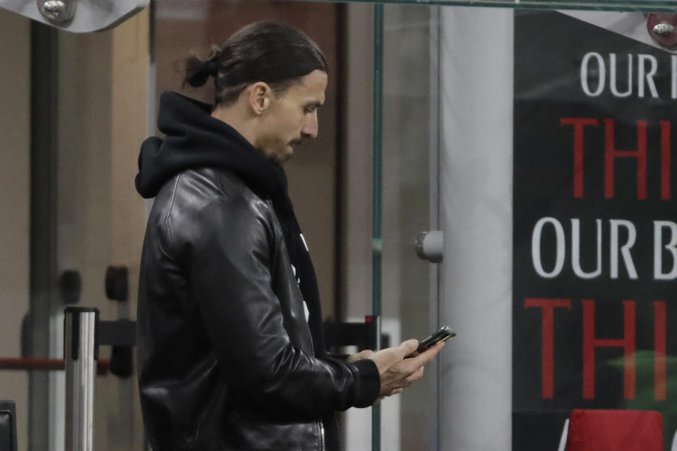 AC Milan's Zlatan Ibrahimovic uses his mobile phone during a Serie A soccer match between AC Milan and Napoli, at the San Siro stadium in Milan, Italy, Sunday, March 14, 2021. (AP Photo/Luca Bruno)