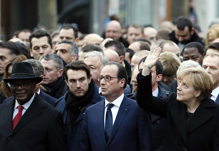 German Chancellor Angela Merkel (R) waves while taking part with French President Francois Hollande (2ndR) and Malian President Ibrahim Boubacar Keita (L) in a unity rally in Paris on January 11, 2015 (AFP Photo/Patrick Kovarik)
