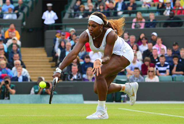 US player Serena Williams returns to France's Alize Cornet during their women's singles third round match in Wimbledon, southwest London, on June 28, 2014 (AFP Photo/Carl Court )