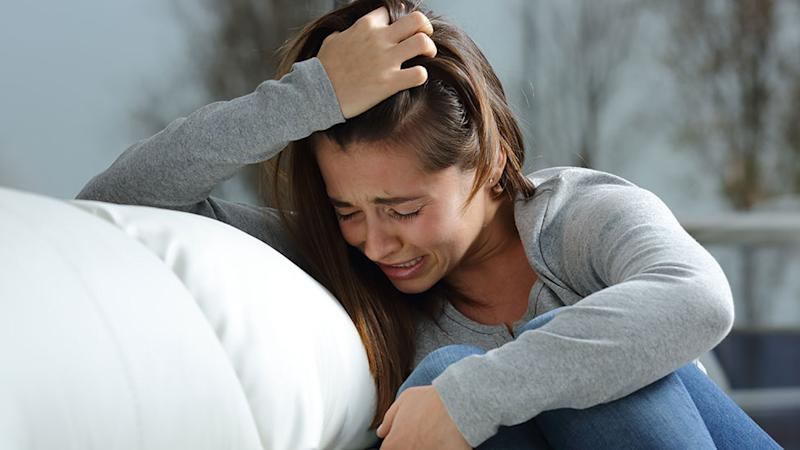 crying woman wearing jeans and a grey weater