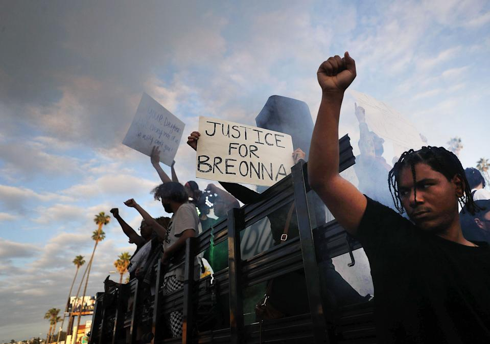 Protesters ride aboard a vehicle with a smoke machine, with a sign reading 'Justice for Breonna', during a peaceful demonstration against racism.