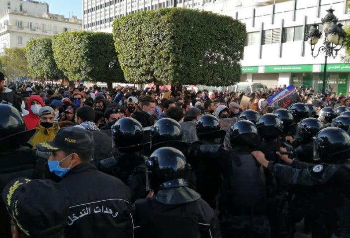 Police officers stand guard as demonstrators take part in an anti-government protest in Tunis