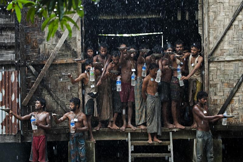Migrants rescued at sea collect rain water at a temporary shelter near the Kanyin Chaung jetty in Rakhine state in June 2015 (AFP Photo/Ye Aung Thu)