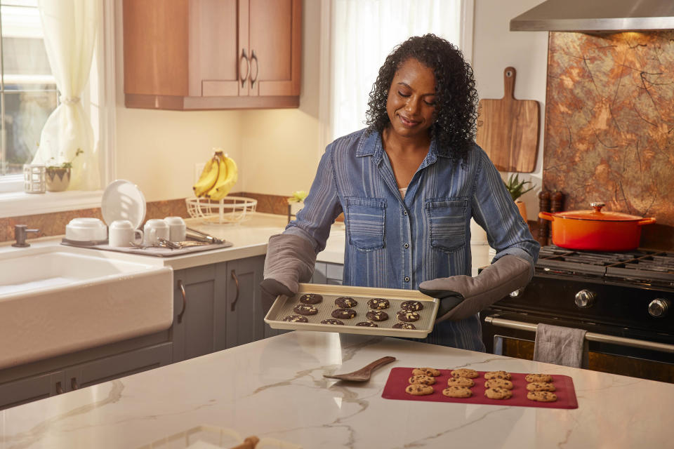 Woman making cookies using cookie sheet and silicone baking sheet from Canadian Tire