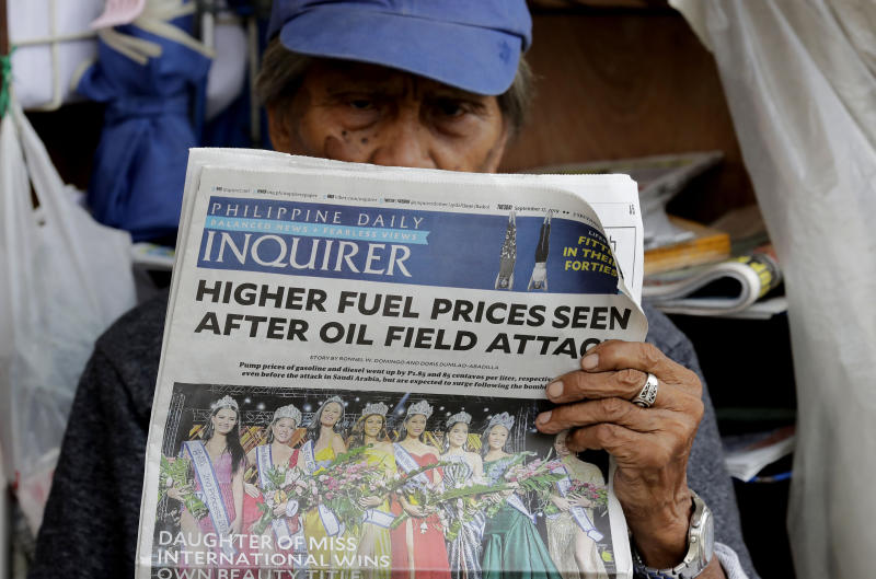 A sidewalk vendor reads a newspaper that headlines the recent attacks of Saudi oil refinery and raises global concern for a possible spike of oil prices Tuesday, Sept. 17, 2019, in Manila, Philippines. Monday saw another round of oil price increase in the country which energy officials said is not related to the recent attacks in Saudi Arabia but has cautioned the public to brace for more spikes in the coming days. (AP Photo/Bullit Marquez)