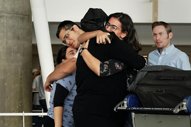 People hug after arriving in advance of the travel ban to the U.S. at John F. Kennedy airport inNew York City, on June 29.