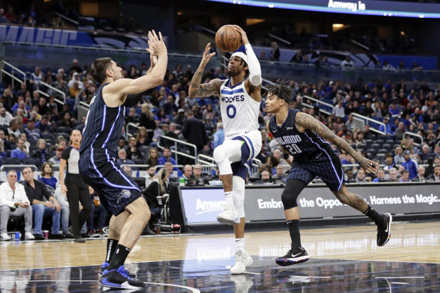 Minnesota Timberwolves guard D'Angelo Russell (0) goes up for a shot between Orlando Magic center Nikola Vucevic, left, and guard Markelle Fultz (20) during the first half of an NBA basketball game Friday, Feb. 28, 2020, in Orlando, Fla. (AP Photo/John Raoux)