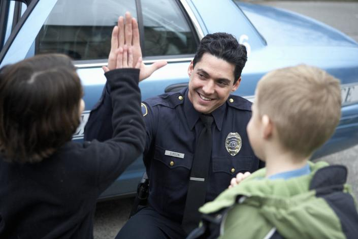 """<span class=""""caption"""">For police officers, building trust is a key part of their job. </span> <span class=""""attribution""""><a class=""""link rapid-noclick-resp"""" href=""""https://www.gettyimages.com/detail/photo/male-police-officer-high-fiving-a-young-boy-royalty-free-image/76536234"""" rel=""""nofollow noopener"""" target=""""_blank"""" data-ylk=""""slk:UpperCut via Getty Images"""">UpperCut via Getty Images</a></span>"""